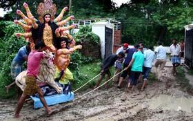 (تصاویر) حمل نمادمذهبی در هند در شرایط بارانی در الله آباد هند