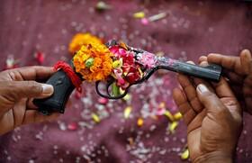 (تصاویر) پلیسی در هند سلاح خودرا برای دعای در روز چشن مذهبی آماده کرده است
