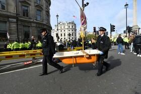 (تصاویر) پلیس انگلیس یک وان حمام را از میدان ترافالگار در لندن که تظاهرکنندگان ضد تخریب محیط زیستی برای راهبندان به خیابن آورده اند انتقال می دهند