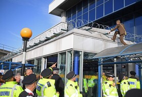 (تصاویر) یکی از معترضان به تخریب محیط زیست در لندن به سقف ورودی فرودگاه لندن رفته است و پلیس تلاش می کند مانع او شود