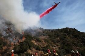 (تصاویر) یک هواپیمای آتش نشان در لوس آنجلس در حال ریختن آب در منطقه در حال سوختن جنگلی
