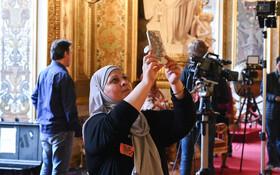 (تصاویر) زن مسلمان جهانگردی در حال دیدار از قصر سنات در پاریس و تصویر برداری با گوشی موبایل