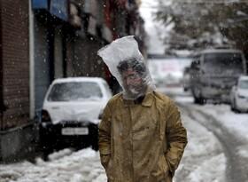 (تصاویر) بارندگی در سرینگر کشمیر هند و مردی که با کیسه پلاستیکی خودرا از بارن محفوظ داشته