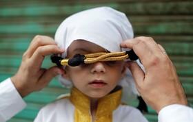 (تصاویر) پدری در دهلی هند فرزندش را با پوشاندن لباس نو برای مراسم میلاد پیامبر اکرم آماده می کند