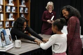 (تصاویر) میشل اوباما  همسر رییس جمهوری سابق آمریکا در مراسم امضای کتابش در واشنگتن با یک مراجعه کننده دیدار می کند