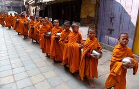 (تصاویر) نوآموزان بودایی در کاتماندو نپال در حال عبور از یک منطقه در این شهر