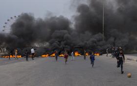 (تصاویر) بازی فوتبال کودکان عراقی در کنار گروهی از تظاهرکنندگان که با آتش زدن لاستیک خیابانی را مسدود کرده اند در بغداد