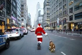(تصاویر) بابانوئل در نیویورک همراه سگش اسکیت سواری می کند