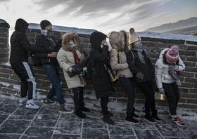 (تصاویر) جهانگردان روی دیوار یخزده چین با توفان مقابله می کنند