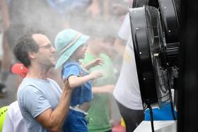 (تصاویر) خنک شدن کودکی در گرمای ملبورن در مقابل پنکه آب پاش در جریان بازی های تنیس  بین المللی در این کشور