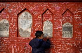 (تصاویر) پسری در کاتماندو نپال در حال نوشتن روی دیوار معبد خدای آموزش