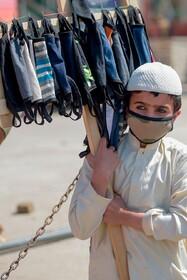 (تصاویر) کودکی در اسلام آباد پاکستان ماسک های دست ساز می فروشد