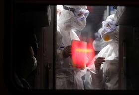 (تصاویر) ماموران بهداشتی در اوکراین در حال بررسی مسافران قطاری که از لیتوانی به این کشور وارد می شود