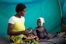 (تصاویر) کودکی در کنگو در قرنطینه با مادرش عذا می خورد وی به سرخک مبتلا شده است