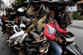 (تصاویر) موتورسواری که کفش های دست دوم را می فروشد در کامبوج