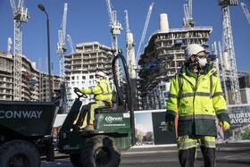 (تصاویر) کارکنان در یک طرح ساحتمانی با ماسک و رعایت فاصله در حال ادامه کار هستند