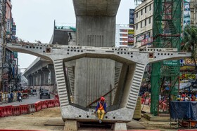 (تصاویر) کارگری در داکای بنگلادش درحال استراحت در جریان ساخت طرح ساخت قطار هوایی