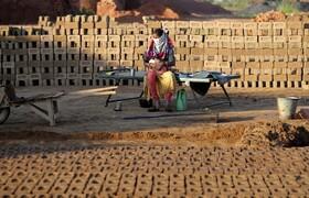 (تصاویر) کارگری در کارگاه آجرپزی در هند کودکش را نگهداری می کند