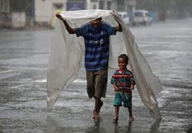 (تصاویر) بی خانمانی در کلکته هند همراه فرزندش در باران