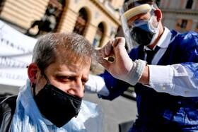 (تصاویر) سلمانی در مقابل اداره اقتصاد ناپل در ایتالیا در اعتراض به متوقف شدن فعالیت این صنف
