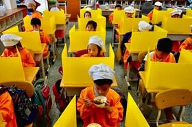 (تصاویر) غذاخوردن کودکان در مدرسه ای در تایپه تایوان برای جلوگیری از انتشار و شیوع ویروس کرونا