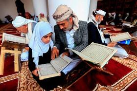 (تصاویر) مردی در کنار دخترش در مسجدی در صنعا یمن قرآن می خواند در ماه رمضان