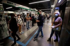 (تصاویر) مسافران در ایستگاه مترویی در رم روی نقاط تعیین شده ایستاتده اند و ماسک دارند