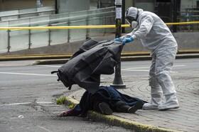 (تصاویر) جسد زنی در کنار خیابان در کیتو در اکوادور توسط یک مامور پوشانده می شود وی به کرونا مبتلا بوده