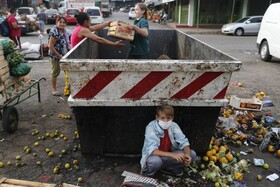 (تصاویر) جمع آوری میوه های دور ریخته شده در بازار میوه پاراگوئه توسط کودکان کار