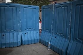 (تصاویر) کودکی در ووهان در کنار محدوده انجام آزمایش کرونا که مقامات همه ساکنان را آزمایش می کنند