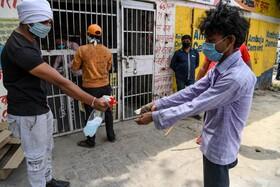(تصاویر) مغازه داری در هند مشتری را با مایع ضد عفونی همیاری می کند