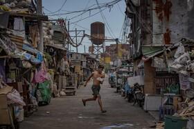 (تصاویر) یکی از ساکنان زاغه نشینی در مانیل برای دیده نشدن توسط نیروهای پلیس از محلی به محل دیگر می دود