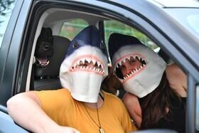 (تصاویر) ماسک کوسه مادر و پسری که برای تماشای فیلم عازم پارکینگی در آتلانتای آمریکا برای تماشای فیلم در ماشین هستند