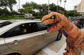 (تصاویر) کودکان توسط فردی که لباس دایناسور به تن کرده سرگرم می شوند