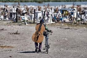 (تصاویر) نوازنده دوره گرد در مکزیک برای مراسم عزاداری بسوی یک قبرستان می رود