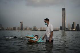 (تصاویر) بازی کودکی در پارک آب گرفته در اثر سیل در ووهان چین