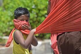 (تصاویر)کودکی در هند با شال مادرش ماسک ساخته