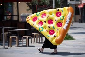(تصاویر) بارسلونای اسپانیا و زنی که یک قطعه پیتزای بادی را حمل می کند