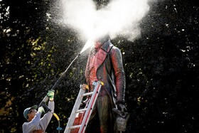 (تصاویر) پاکسازی مجسمه بانکدار قرن هجدهم سوئیسی که در تجارت برده نقش داشته از رنگ قرمزی که تظاهرکنندگان بروی آ« ریخته اند