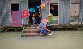 (تصاویر) زنی در کنار خانه ظرفی را در سیل بنگلادش می شورد
