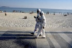 (تصاویر) زن و مرد سالمندی در ریودوژانیرو در لباس فضانوردی برای پیش گیری از بیماری کرونا در ساحلی قدم می زنند