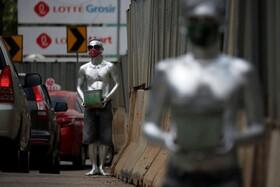 (تصاویر) مردان موسوم به مردان نقره ای در کنار خیابانی در جاکارتای اندونزی صدقه جمع آوری می کنند
