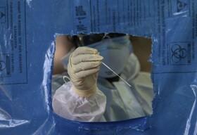 یک کارمند خدمات بهداشتی در حیدر آباد هند در حال گرفتن آزمایش کرونا