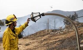 کج شدن جراغ خیابانی در اثر آتش سوزی در کالیفرنیای آمریکا